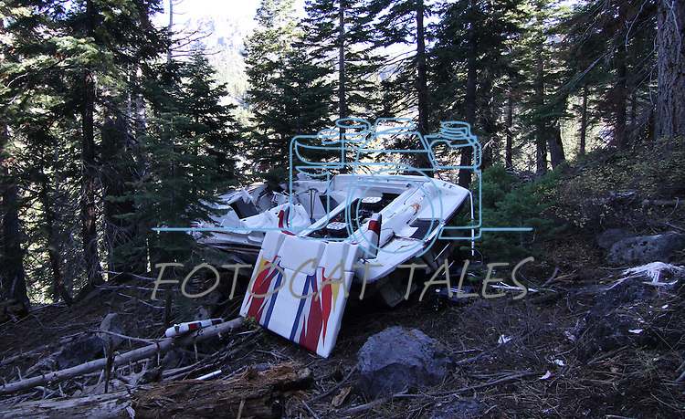 A 35' Mercruiser rests about 1000 feet below Highway 4 in Alpine County following an accident last Tuesday, while crews work nearby to remove wreckage from an unrelated truck and trailer accident from Aug. 2010, that also occurred on Cadillac Curve, south of Markleeville, Ca. on Tuesday, Oct. 12, 2010. The drivers involved in both accidents were uninjured..Photo by Cathleen Allison