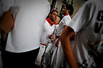 A young man is seen in Estafeta street during the San Fermin Festival, on July 7, 2012, in Pamplona, northern Spain. The festival is a symbol of Spanish culture that attracts thousands of tourists to watch the bull runs despite heavy condemnation from animal rights groups . (c) Pedro ARMESTRE