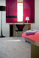 A pair of bold purple blinds hangs across the round bedroom window