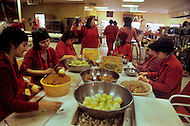 Wasco, Oregon, January 1984: Disciples of Bhagwan Rajneesh, preparing vegetarian meals in the community kitchen, which would be served in the lunchroom. Most of the food came from the community ranch.  Rajneeshpuram, was an intentional community in Wasco County, Oregon, briefly incorporated as a city in the 1980s, which was populated with followers of the spiritual teacher Osho, then known as Bhagwan Shree Rajneesh. The community was developed by turning a ranch from an empty rural property into a city complete with typical urban infrastructure, with population of about 7000 followers.