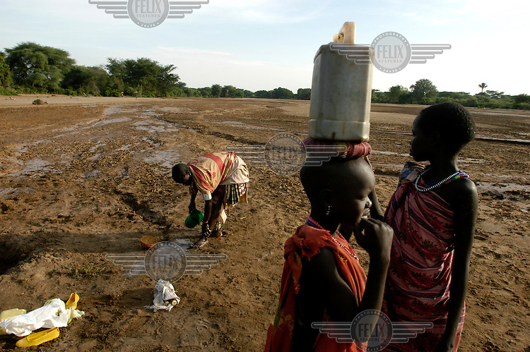 Toposa tribe women draw water from a hole dug in the dry bed of the Singaita River in Eastern Equatoria province. Failed rainy seasons have severely affected several East African countries.