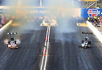 Feb 23, 2014; Chandler, AZ, USA; Both NHRA top fuel dragster driver Doug Kalitta (left) and Khalid Albalooshi have a peddlefest getting sideways during the Carquest Auto Parts Nationals at Wild Horse Motorsports Park. Mandatory Credit: Mark J. Rebilas-USA TODAY Sports