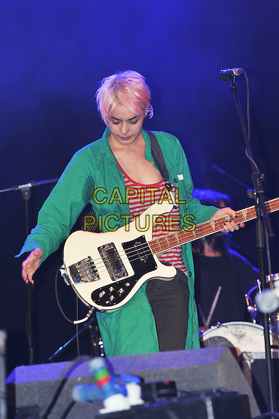 WARPAINT - Jenny Lee Lindberg.Performing live on Day 3 at the Reading Festival, Reading, England..August 28th, 2011.stage concert live gig performance music half length green jacket red stripe top bass guitar armpit sweat patch .CAP/MAR.© Martin Harris/Capital Pictures.