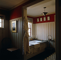 A contemporary bath in a bathroom decorated in pale cream painted pine-cladding with a red paint-effect