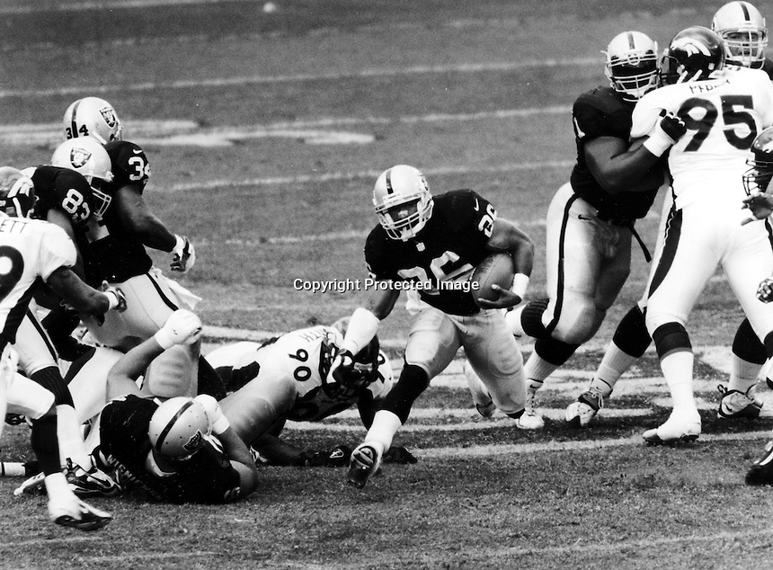 Napoleon Kaufman runs thru hole for the Raiders. .Photo by Ron Riesterer