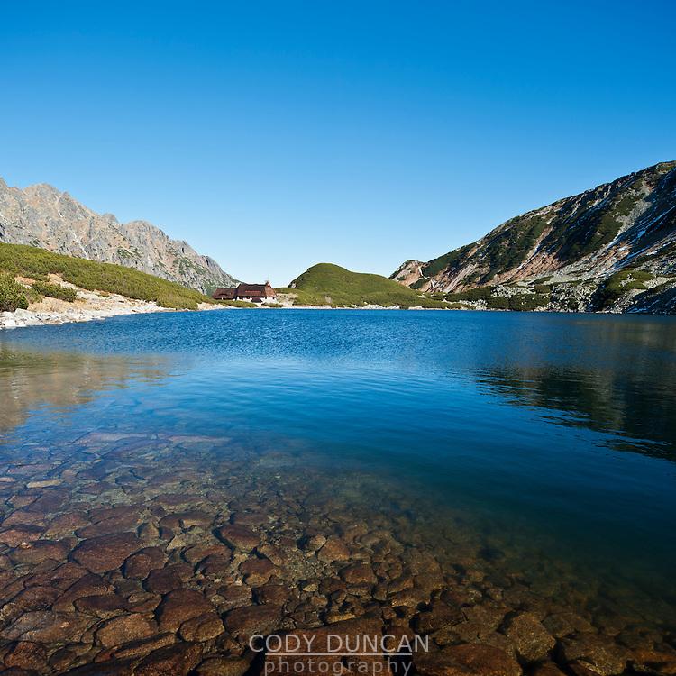 View across Przedni Staw - Front lake towards mountain hut, Five Lakes Valley, Tatra mountains, Poland