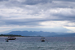 The view across the water to Bali from Gili Trawangan, Lombok, Indonesia. Cloudy sky and fishing boats fill the horizon.