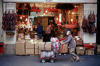 Another stallholder pushes a trolley of goods past an open air dried goods shop near Hong Kong Central's market.