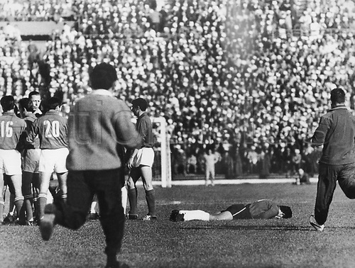 Tumultuous scenes during the 1962 World Cup match Chile versus Italy at the National Stadium in Santiago de Chile, Chile, 2 June 1962. Medical attendants rush towards a Chilean player who lies injured on the ground while British referee Ken Aston (3rd from L) is surrounded by the Italian defenders Robotti (L, no 16) and midfielder Tumburus (2nd from L, no 20).  Chile won the game 2-0 in front of 66,000 spectators. The game was considered to be a scandal due to a continued series of fouls and assaults on the pitch which disrupted the game. Two Italian players were sent off andone player only left when police officers escorted him off the pitch.