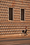 Woman on a bike by the diamond wall of the Palazzo dei Diamanti, originally a residential home of the Este family (built between 1493 and 1503) and acquired by the city in 1832, the palace is now the National Gallery of Art and Civic University