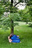 A man in a sleeping bag beneath a tree in Regents Park, London.