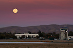 Full moon rising over Control Tower and runwayy at Buchanan Field Airport, Concord, California