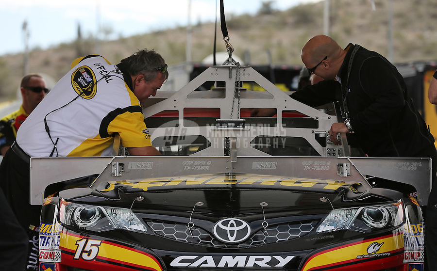 Mar. 3, 2013; Avondale, AZ, USA; NASCAR Sprint Cup Series officials inspect the car of Clint Bowyer in the garage prior to the Subway Fresh Fit 500 at Phoenix International Raceway. Mandatory Credit: Mark J. Rebilas-