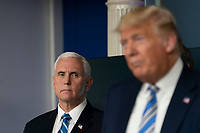 United States Vice President Mike Pence listens as US President Donald J. Trump speaks during a news briefing by members of the Coronavirus Task Force at the White House in Washington, DC on Monday, March 23, 2020.<br /> Credit: Chris Kleponis / Pool via CNP/AdMedia