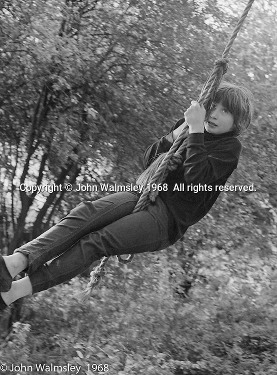 Swinging on a rope from a tree in the grounds, Summerhill school, Leiston, Suffolk, UK. 1968.