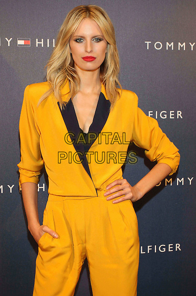 Karolina Kurkova.Tommy Hilfiger Store Opening Cocktail party, Hamburg, Germany..November 16th, 2011.half length black yellow playsuit hand on hip red lipstick .CAP/PPG.©People Picture/Capital Pictures