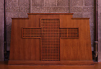 Wooden confessional with lattice in the shape of a cross, in the Eglise Saint-Joseph or St Joseph's Church, built 1951-58 as a memorial to the 5000 citizens of the town who died during the Second World War, designed by Auguste Perret, 1874-1954, and Raymond Audigier, Le Havre, Normandy, France. The church is built from pre-cast concrete, with geometric stained glass windows by Marguerite Hure, a Neo-Gothic interior and a 107m tall tower which acts as a beacon from out at sea. Perret was mentor to Le Corbusier and specialised in the use of concrete. He led the reconstruction of Le Havre in the 1950s, after the town was completely destroyed in WWII. The centre of Le Havre is listed as a UNESCO World Heritage Site. Picture by Manuel Cohen