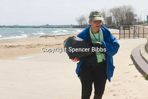 Saturday, April 22nd, 2017 was Earth Day and the Jackson Park Advisory Council stepped up with various projects around the neighborhood.<br /> <br /> 2588 &ndash; President of the Jackson Park Advisory Council, Louise Mcurry carries away garbage at the 57th Street Beach.<br /> <br /> Please 'Like' &quot;Spencer Bibbs Photography&quot; on Facebook.<br /> <br /> All rights to this photo are owned by Spencer Bibbs of Spencer Bibbs Photography and may only be used in any way shape or form, whole or in part with written permission by the owner of the photo, Spencer Bibbs.<br /> <br /> For all of your photography needs, please contact Spencer Bibbs at 773-895-4744. I can also be reached in the following ways:<br /> <br /> Website &ndash; www.spbdigitalconcepts.photoshelter.com<br /> <br /> Text - Text &ldquo;Spencer Bibbs&rdquo; to 72727<br /> <br /> Email &ndash; spencerbibbsphotography@yahoo.com
