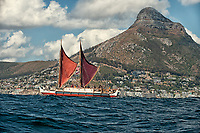 "Voyaging canoe Hokule'a sails toward Cape Town, South Africa, with Lino's Head (mountain peak) in the distance, Thursday, November 12, 2015. Hokule'a was on a ""Malama Honua"" (Care for the Earth) worldwide voyage to raise awareness about the importance of protecting the world's oceans, considered the greatest environmental challenge of our time."