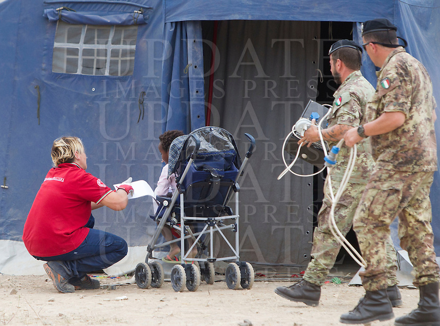 Un'operatrice della Croce Rossa gioca con una bambina nella tendopoli allestita presso la stazione Tiburtina a Roma, 16 giugno 2015.<br />