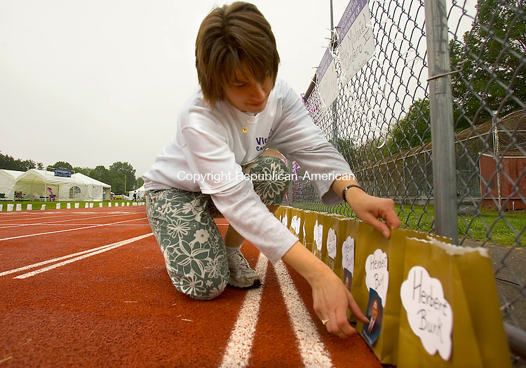 CHESHIRE, CT --JUNE 06, 2008-060608JS02-Joy Renner of Tolland, places photos of family members on memorial luminary bags around the Cheshire High School track as part of the annual Relay For Life on Friday. <br /> Jim Shannon/Republican-American