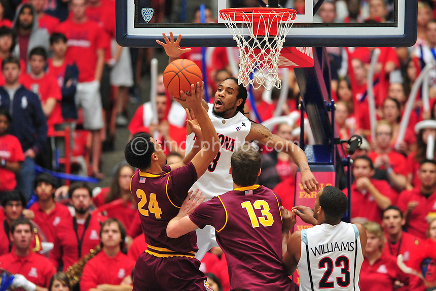 Jan 15, 2011; Tucson, AZ, USA; Arizona Wildcats forward Jesse Perry (33) tries to block the shot of Arizona State Sun Devils guard Trent Lockett (24) in the 2nd half of a game at the McKale Center.  The Wildcats won the game 80-69.