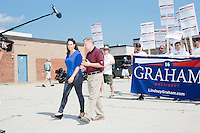Republican presidential candidate Lindsey Graham is interviewed by a television reporter before marching in the Labor Day parade in Milford, New Hampshire.  Republican candidates John Kasich, Carly Fiorina, and Democratic candidate Bernie Sanders also marched in the parade.