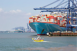 Small foot ferry passenger boat dwarfed by huge Edith Maersk container ship, Port of Felixstowe, Suffolk, England, UK