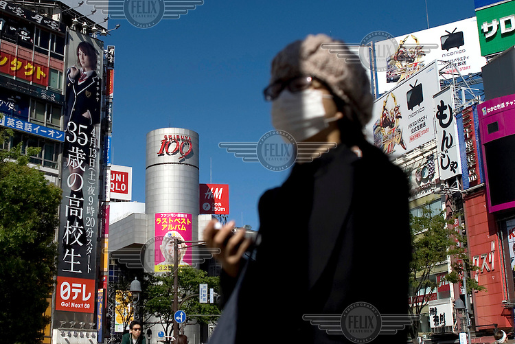 A woman crosses the road in Shibuya. She wears a surgical mask, a common sight in Asia. Rising from street level behind her is a cluttered mass of advertising hordings and shop signs. /Felix Features