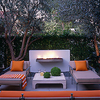 The 'outdoor living room' is shaded by mature olive trees and shielded from the street by a dense ficus hedge and has a freestanding fireplace as its focal point