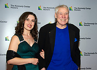 Jacques d'Amboise, right, and Emily Reid  arrive for the formal Artist's Dinner honoring the recipients of the 41st Annual Kennedy Center Honors hosted by United States Deputy Secretary of State John J. Sullivan at the US Department of State in Washington, D.C. on Saturday, December 1, 2018. The 2018 honorees are: singer and actress Cher; composer and pianist Philip Glass; Country music entertainer Reba McEntire; and jazz saxophonist and composer Wayne Shorter. This year, the co-creators of Hamilton, writer and actor Lin-Manuel Miranda, director Thomas Kail, choreographer Andy Blankenbuehler, and music director Alex Lacamoire will receive a unique Kennedy Center Honors as trailblazing creators of a transformative work that defies category.<br /> CAP/MPI/RS<br /> &copy;RS/MPI/Capital Pictures