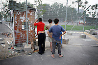 """CHINA. Beijing. Men peer through a fence, trying to catch a glimpse of the new Olympic park. In recent years construction has boomed in Beijing as a result of the country's widespread economic growth and the awarding of the 2008 Summer Olympics to the city. For Beijing's residents however, it seems as their city is continually under construction with old neighborhoods regularly being razed and new apartments, office blocks and sports venues appearing in their place. A new Beijing has been promised to the people to act as a showcase to the world for the 'new' China. Beijing's residents have been waiting for this promised change for years and are still waiting, asking the question """"Where's the new Beijing?!"""". 2008."""