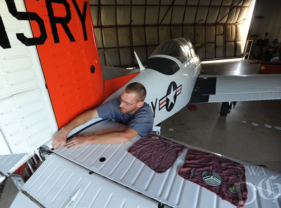 NWA Media/ANDY SHUPE - Dustin Thompson, a technician with Devol Aviation, reinstalls trim around the base of the vertical stabilizer of a Beechcraft T-34 Mentor Thursday, Aug. 21, 2014, in a hangar at Drake Field in Fayetteville. The plane is a former Naval training aircraft from the Vietnam War era that is owned by a Fayetteville businessman and was receiving its required yearly inspection.