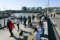 BNPS.co.uk (01202 558833)<br /> Pic: Graham Hunt/BNPS<br /> <br /> Visitors not put off by the coronavirus pandemic flock to the seaside resort of West Bay in Dorset on a day of sunshine and clear blue skies.<br /> <br /> Visitors walking next to the harbour taking no notice of the advice given about social distancing.