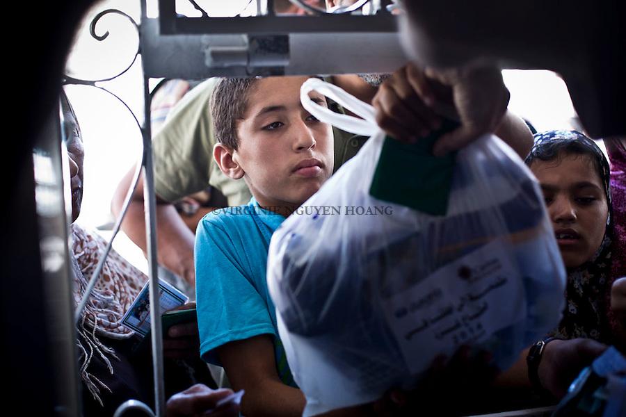 GAZA: A refugee child is taking a donations bag from a Caritas Jerusalem member in Saint Porphyrios Church. 1st August 2014. <br /> <br /> GAZA: Un enfant r&eacute;fugi&eacute; re&ccedil;oit un sac de dons d'un membre d'une NGO internationale dans l'&eacute;glise Saint Porphyre. 1st Ao&ucirc;t 2014.