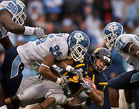 West Virginia quarterback Pat White (5) is tackled by North Carolina linebacker Brian White (94) during the Meineke Car Care Bowl college football game at Bank of America Stadium in Charlotte, NC.
