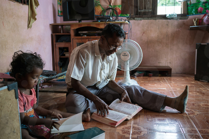 November 27, 2016 - Pailin (Cambodia). Sok Sem (58) reads his bible together with his smaller daughter Sok Sreypao (4). Sok was a commander of a special military unit of the Khmer Rouge and he converted to christianity in 2001. © Thomas Cristofoletti / Ruom