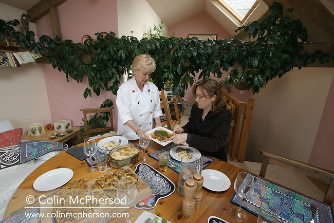 Annette Gibbons (left) of Cumbria On A Plate, serving a meal in the dining room of her home in Mawbray, Cumbria to writer Fiona Sims. Annette hosts slow food safaris, a tourism business which guides visitors around various Cumbrian food producers and rounds off with a meal cooked in her house. Annette is the Cumbrian Woman of the Year and has a recently-published book on Cumbrian food.