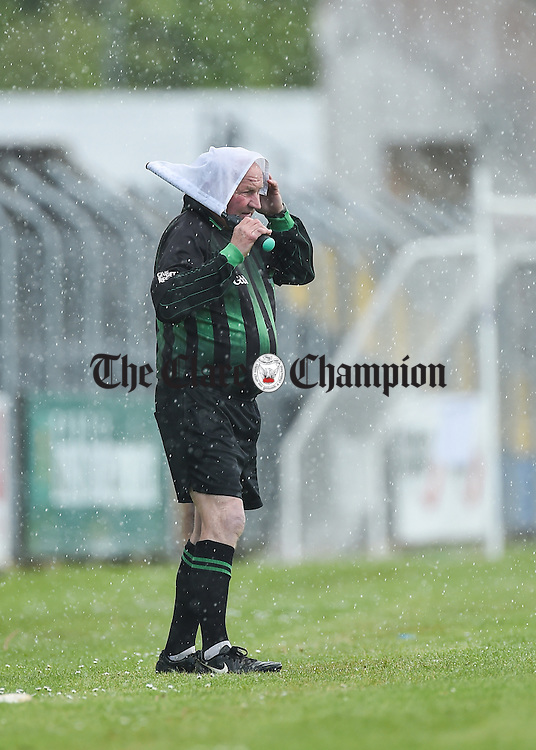 Linesman Michael Fitzgerald of Clondegad had to call on all his resources to stave off the bad weather in Cusack park during the senior championship hurling game between Tulla and Clooney-Quin on Sunday. Photograph by John Kelly.