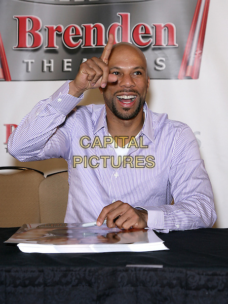 "COMMON (Lonnie Rashied Lynn, Jr.).Common celebrates the release of his movie, ""Just Wright"" at Brenden Theaters at the Palms Resort Hotel and Casino, Las Vegas, Nevada, USA, .14th May 2010..half length purple white pinstripe shirt sitting signing  beard facial hair hand smiling finger gesture .CAP/ADM/MJT.© MJT/AdMedia/Capital Pictures."