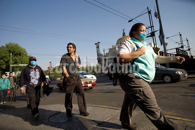 People wearing  protective mask to prevent swine flu, walk through a normally overcrowded avenue now plenty of room in Mexico DF.Few people still dares to walk the streets or take the public transportation as epidemic spreads fast in Mexico
