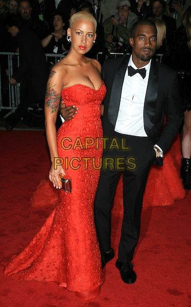 "AMBER ROSE & KANYE WEST .Arrivals for the Met Costume Institute Gala Benefit - ""The Model as Muse: Embodying Fashion"" at the Metropolitan Museum of Art, New York, NY, USA, .May 4th 2009..Full length strapless red dress print tattoos tattoo couple black suit tux tuxedo bow tie gold clutch bag cleavage .CAP/LNC/TOM.©LNC/Capital Pictures"
