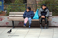 Pictured: Two girls rest on a bench in Victoria Square Wednesday 09 March 2016<br /> Re: Migrants at Victoria Square, in central Athens, Greece.