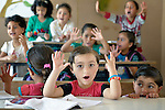 Children participate in math class in a school in a settlement of Syrian refugees in Minyara, a village in the Akkar district of northern Lebanon. Lebanon hosts some 1.5 million refugees from Syria, yet allows no large camps to be established. So refugees have moved into poor neighborhoods or established small informal settlements in border areas. International Orthodox Christian Charities, a member of the ACT Alliance, provides a variety of assistance to families in this settlement, including support for education.