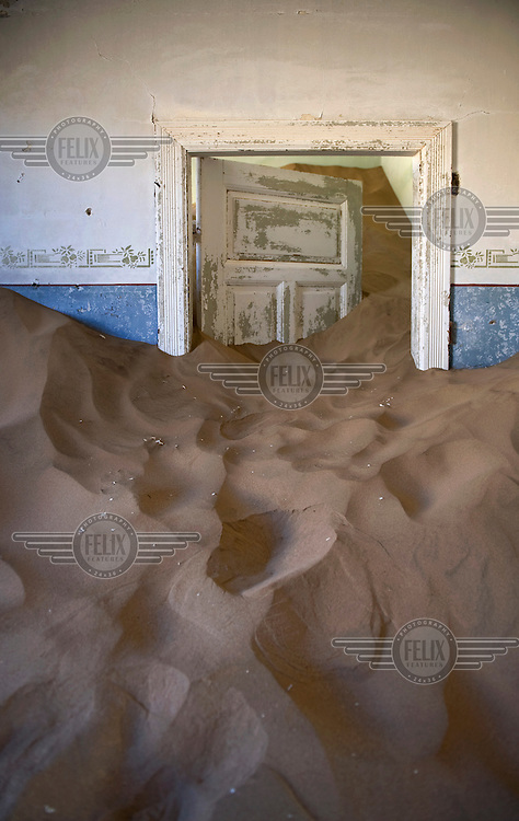 The interior of a house, fallen into disrepair and overcome by sand. Under colonial rule, the German founded diamond mining community was buzzing from 1908 untill it was abandoned in the 1950's. It is now a restricted zone, where access is forbidden.