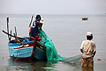 Fishermen pull a net into their boat in the flat sea off Mui Ne, Vietnam. Nov. 20, 2011.