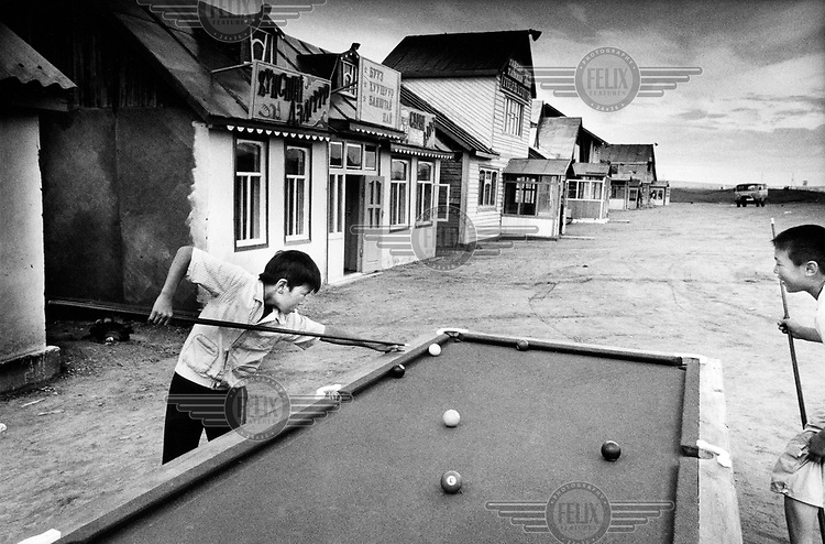 Two boys playing pool outside a cafe for passing drivers, next to the one and only paved road in the country.