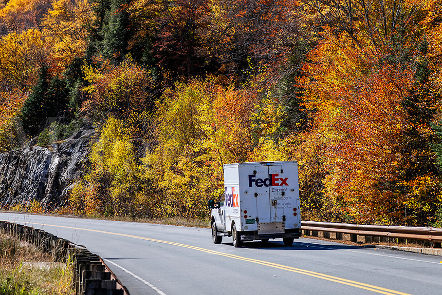 FedEx delivery truck making autumn delivery.
