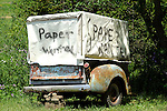 Old pick-up truck bed with 'Paper Wanted' sign.