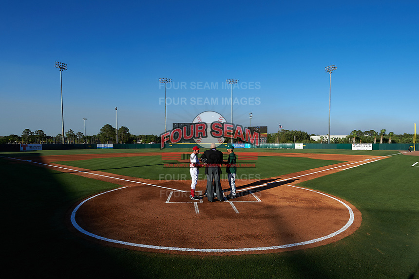 Florida Fire Frogs coach Paul Runge (12) during the lineup exchange with manager Eli Marrero (right) and umpires Jose Navas and Tyler Jones (hidden) before a game against the Daytona Tortugas on April 6, 2017 at Osceola County Stadium in Kissimmee, Florida.  Daytona defeated Florida 3-1.  (Mike Janes/Four Seam Images)